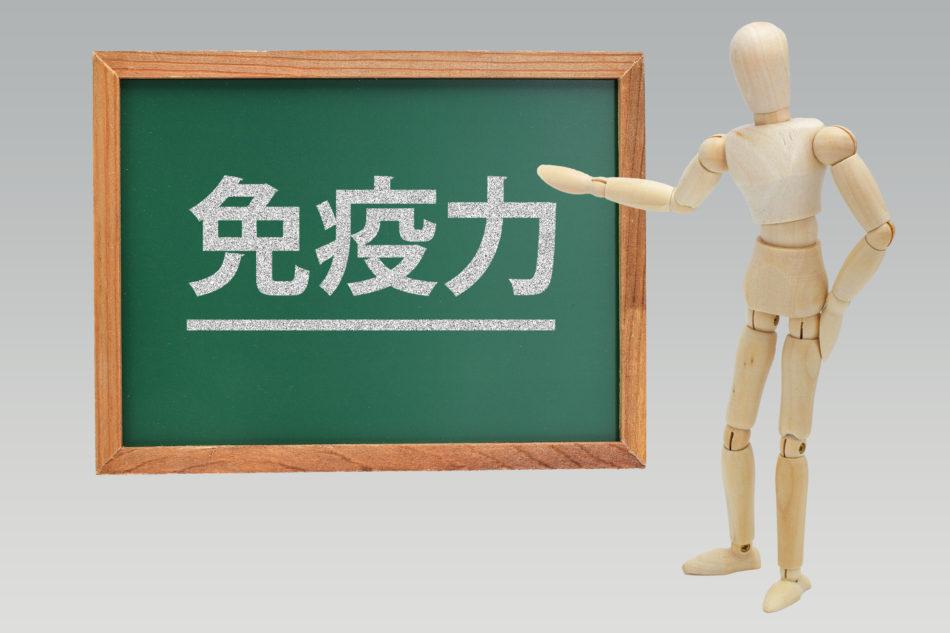 免疫力と表示された黒板を案内する気のロボット
