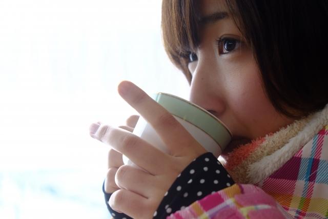 お茶を飲んで温まっている女性のイメージ画像です。