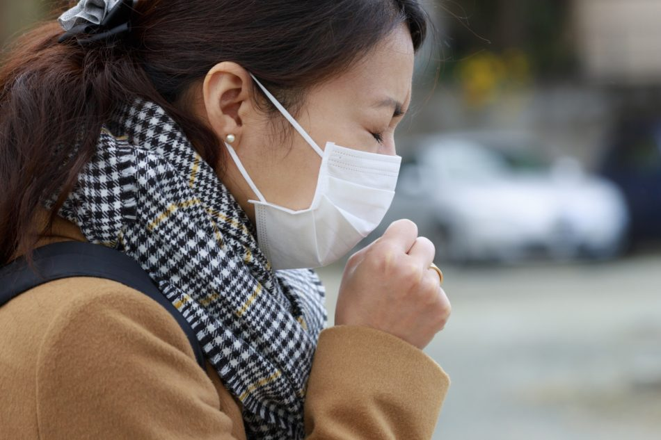 マスクを着用し咳をする女性のイメージ画像