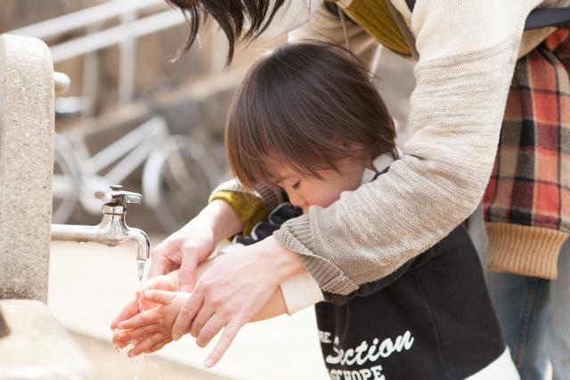 母親と一緒に手を洗う男児