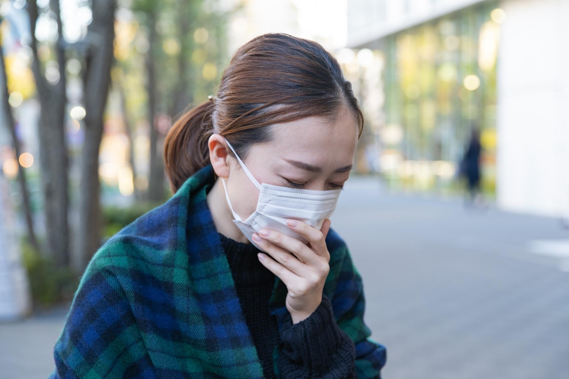 街中でマスクを着用し咳をするOLのイメージ画像です。